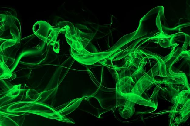 Résumé de fumée verte sur fond noir et concept d'obscurité