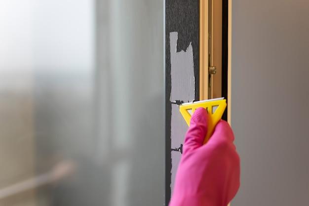 Retirer le ruban de protection du cadre de la fenêtre avec un grattoir