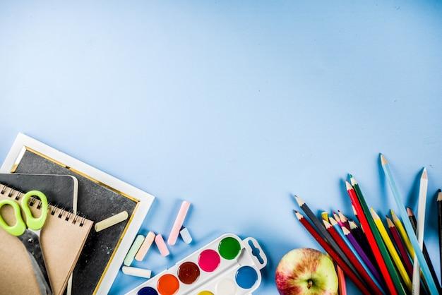 Retour à l'arrière-plan de l'école avec des accessoires pour la salle de classe - peintures, crayons, cahiers, livres, ciseaux, craie, marqueurs, fond bleu, au-dessus de l'espace de copie