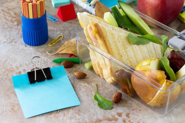 Retour à l'arrière-plan de l'école avec une boîte à lunch et une pomme d'autocollant de fournitures scolaires