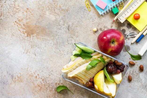 Retour à l'arrière-plan de l'école avec des fournitures scolaires, une boîte à lunch et une pomme, vue de dessus, espace de copie à plat