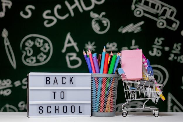 Retour à l'arrière-plan de l'école avec des livres, des crayons et un globe sur tableau blanc sur un fond de tableau noir vert.