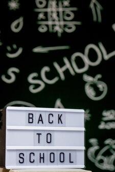 Retour à l'arrière-plan de l'école avec des livres, des crayons et un globe sur un tableau blanc sur un tableau noir