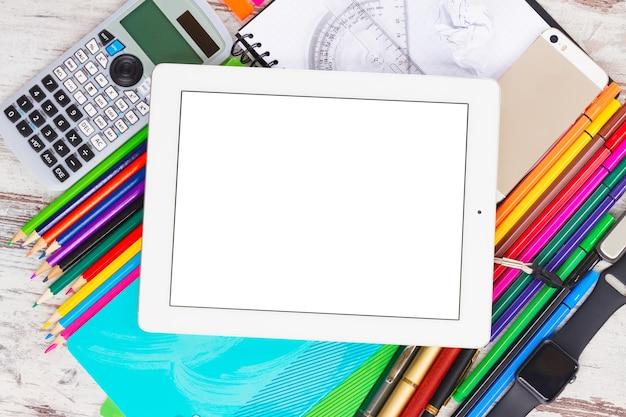 Retour au cadre de l'école avec des fournitures scolaires et tablette d'appareil électronique avec écran vide sur table en bois