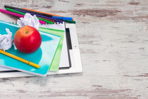 Retour au cadre de l'école avec des fournitures scolaires et tablette avec écran vide sur un bureau en bois