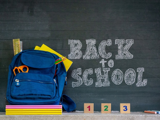 Retour au concept de l'école. cartable avec papeterie et cahiers devant le tableau.
