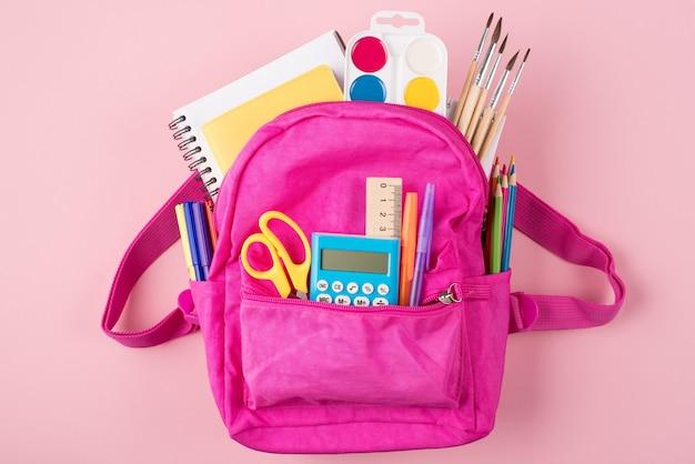 Retour au concept de l'école. concept d'étude. en haut au-dessus de la photo vue de dessus du sac à dos rose et de la papeterie colorée isolée sur fond rose pastel