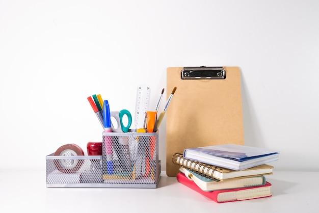 Retour au concept d'école. crayon, stylo et fournitures dans un support sur fond blanc