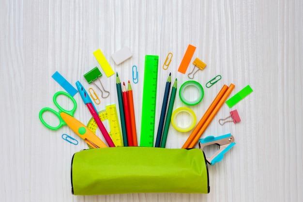 Retour au concept de l'école. étui à crayons avec fournitures de bureau scolaire sur fond de bois blanc.