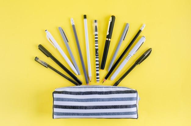 Retour au concept de l'école. étui à crayons avec papeterie scolaire sur fond jaune. papier pour cahier, crayon, trombone et pense-bête avec espace de copie,