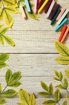 Retour au concept de l'école fond flatlay table avec des feuilles d'automne et différentes fournitures scolaires