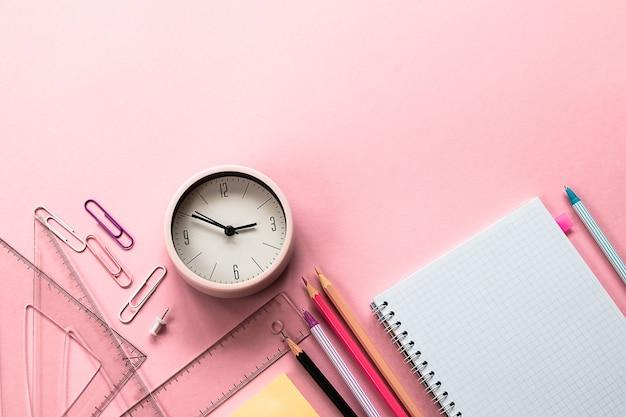 Retour au concept de l'école. fournitures scolaires et de bureau sur fond rose