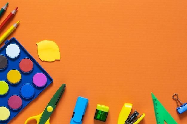 Retour au concept de l'école. fournitures scolaires et de bureau sur la table de bureau. fond orange. mise à plat avec copie espace. automne