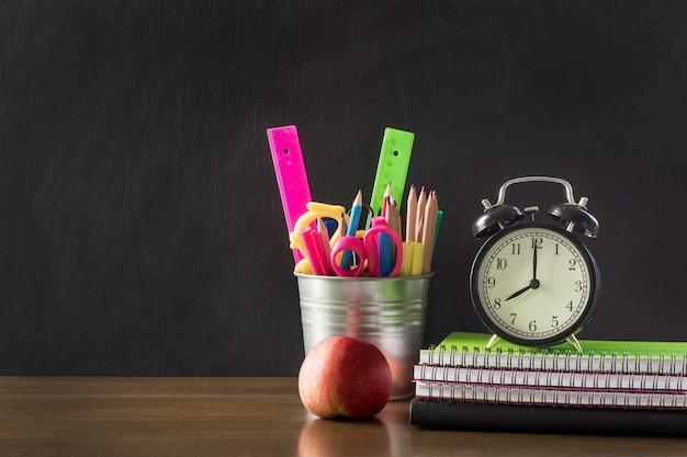 Retour au concept d'école. fournitures scolaires, réveil et pomme.