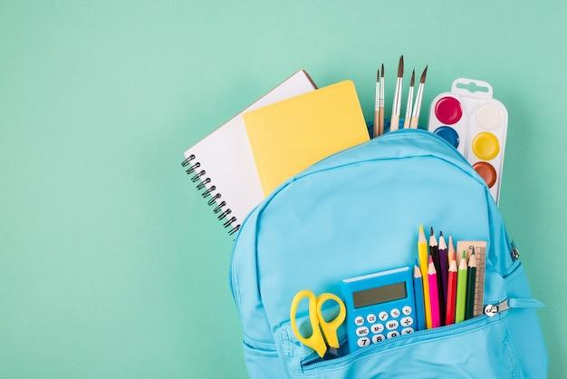 Retour au concept de l'école. en haut au-dessus de la photo vue de dessus du sac à dos bleu complet rempli de papeterie scolaire isolée sur fond turquoise