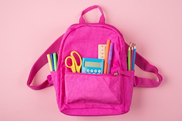 Retour au concept de l'école. en haut au-dessus de la photo vue de dessus du sac à dos rose et de la papeterie colorée isolée sur fond rose pastel