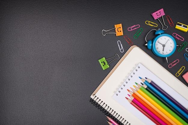 Retour au concept de l'école. haut au-dessus de la vue aérienne photo de papeterie colorée isolée sur tableau noir