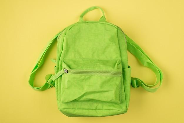 Retour au concept de l'école. haut au-dessus de la vue aérienne photo de sac à dos vert isolé sur fond jaune