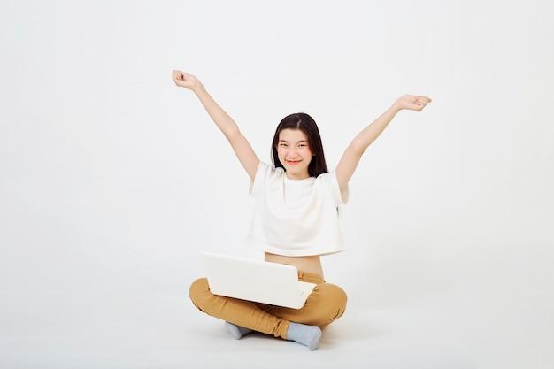 Retour au concept de l'école, heureuse jeune femme asiatique belle attrayante assise sur le sol avec les jambes croisées et utilisant un ordinateur portable