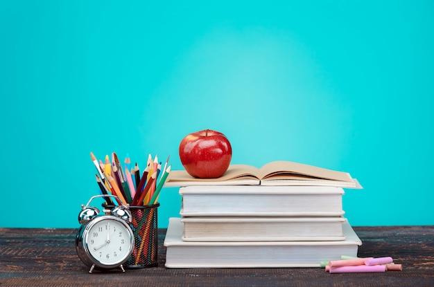 Retour au concept de l'école. livres, crayons de couleur et horloge