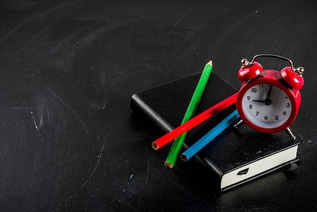 Retour au concept de l'école avec des livres crayons de couleur réveil fond tableau noir