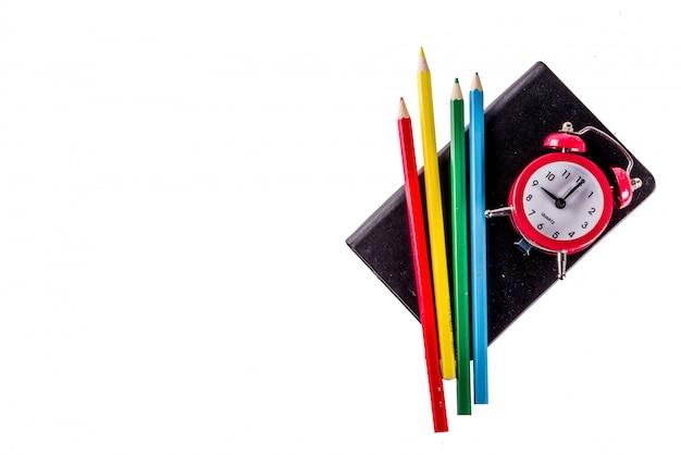 Retour au concept de l'école avec des livres crayons de couleur de réveil isolé sur fond blanc