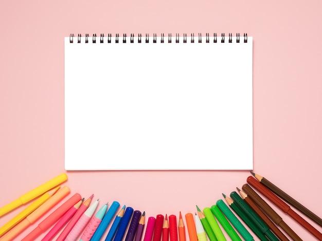 Retour au concept de l'école. maquette cahier et crayons arc-en-ciel sur fond pastel rose.