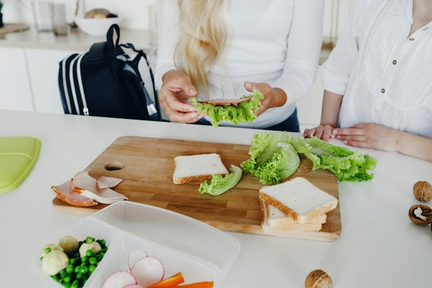 Retour au concept de l'école une mère prépare des sandwichs pour les enfants
