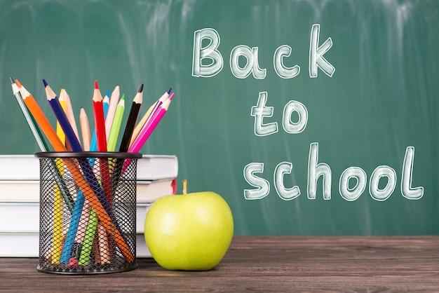 Retour au concept de l'école. photo en gros plan de crayons colorés manuels de pomme verte isolés sur fond de tableau vert