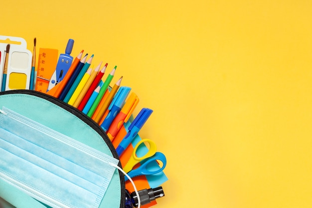 Retour au concept de l'école. sac à dos scolaire bleu complet avec différentes fournitures sur fond jaune. plat poser.