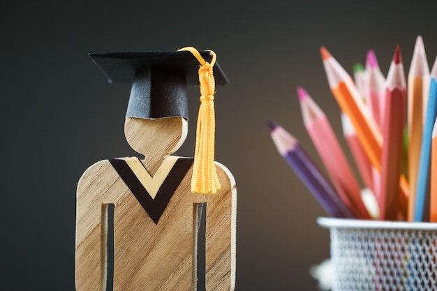 De retour au concept de l'école, signe des gens en bois avec la boîte à crayons flou chapeau graduation