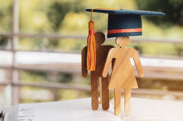 De retour au concept de l'école, signe de gens en bois avec chapeau de graduation célébrant sur un manuel ouvert avec vert clair