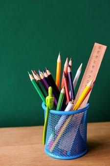 Retour au concept de l'école, verre bleu avec des fournitures scolaires sur un banc d'école