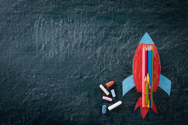 Retour au concept de l'école. vue de dessus de la fusée de papier peint sur un tableau noir.