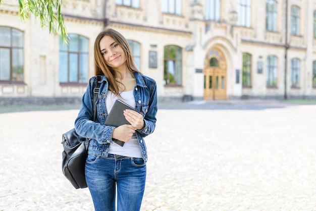 Retour au concept de l'institut ! gros plan photo portrait d'une fille assez intelligente et heureuse avec des cheveux longs portant des vêtements décontractés tenant un journal à la main en regardant la caméra arrière-plan flou automne été