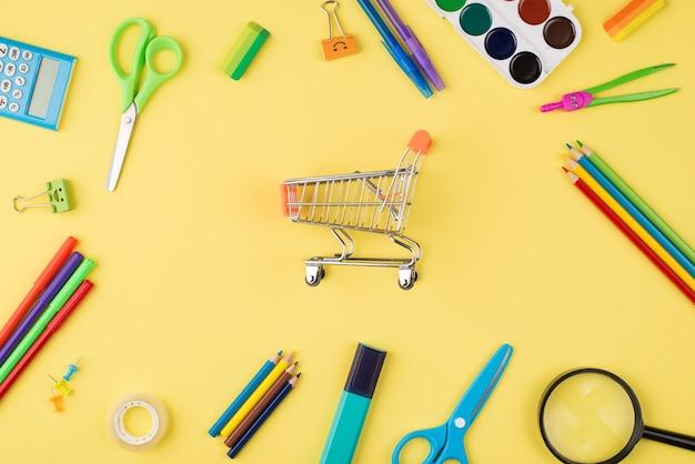Retour au concept de magasinage scolaire. en haut au-dessus de la photo vue de dessus du petit chariot et de la papeterie colorée isolée sur fond jaune