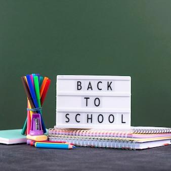 Retour au fond de l'école avec des fournitures scolaires et une boîte à lumière