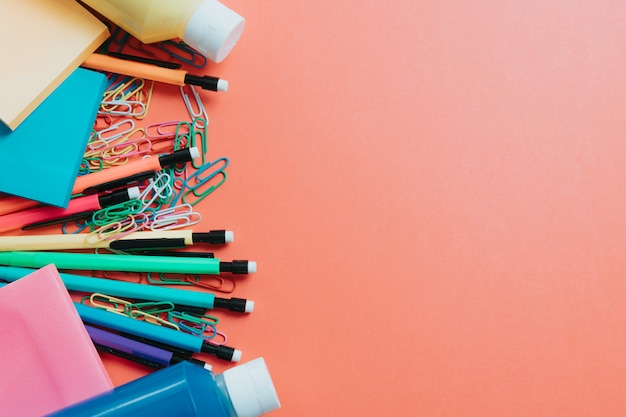 Retour au fond de l'école avec des fournitures scolaires sur le tableau noir. crayons, stylos, carton, fond coloré
