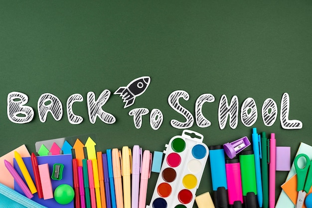 Retour au fond de l'école avec des fournitures scolaires sur vert