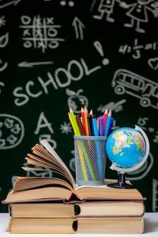 Retour au fond de l'école avec des livres, des crayons et un globe sur un tableau blanc sur un fond de tableau vert.