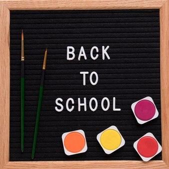 Retour au texte de l'école sur l'ardoise avec des peintures aquarelles colorées et un pinceau