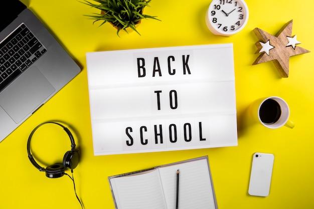 Retour au texte de l'école sur lightbox sur table de travail de bureau jaune moderne
