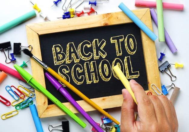 Retour au texte de l'école. main tenant la craie. cadre en bois tableau noir entre école fixe