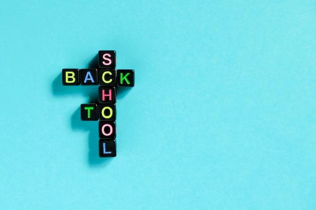Retour au texte de l'école à partir de lettres colorées sur des cubes noirs disposés sous forme de mots croisés