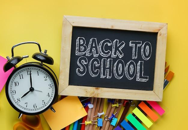 Retour au texte de l'école. réveil, tableau noir et fournitures scolaires sur fond jaune