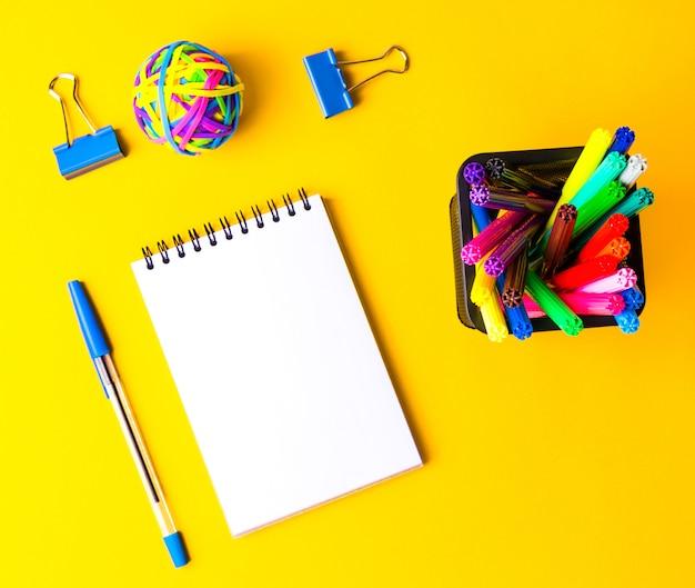 Retour aux fournitures scolaires ou de bureau, fournitures scolaires sur jaune, retour à l'arrière-plan conceptuel de l'école. place pour le texte, vue de dessus.