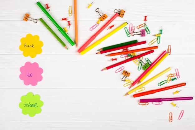 Retour à la bannière de l'école avec papeterie colorée sur fond en bois blanc.