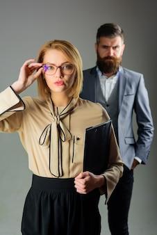 Retour à l'école. 1er septembre. enseignante dans des verres. éducation. travail scolaire. portrait d'une enseignante sensuelle avec bloc-notes. professeur barbu. deux professeurs.