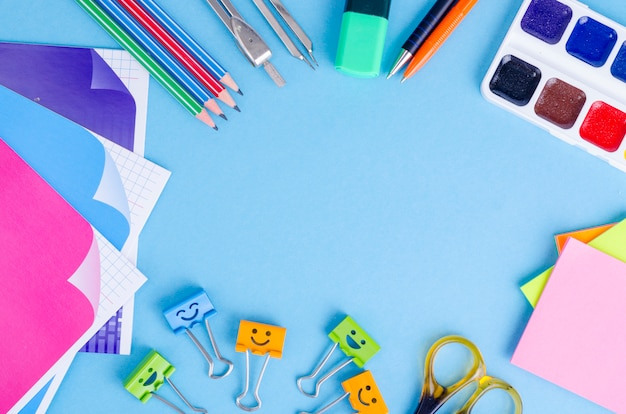 De retour à l'école avec des accessoires scolaires - peintures, crayons, cahiers, ciseaux, marqueurs, fond bleu.