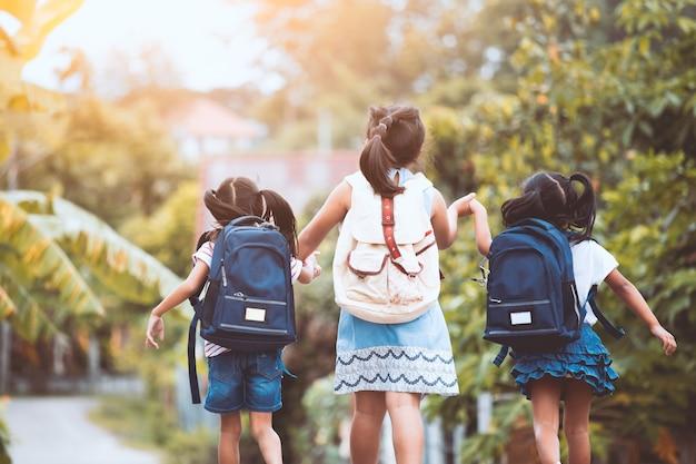 Retour à l'école. asiatique élève enfants avec sac à dos allant à l'école ensemble